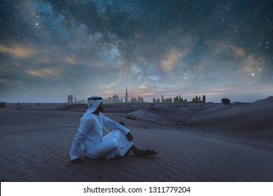 Arabic man with kandura walking in the desert at sunset time