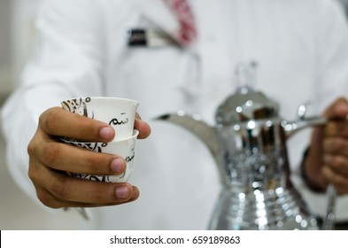 """Arabic man is presenting a cup of Arabic Coffee (the translation of the text appears on the cup: term used in Saudi Arabia means hospitality or it means """"here you are"""" or """"tell me what you want"""")"""