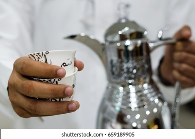 "Arabic man is presenting a cup of Arabic Coffee (the translation of the text appears on the cup: term used in Saudi Arabia means hospitality or it means ""here you are"" or ""tell me what you want"")"