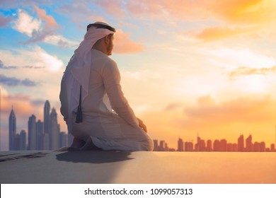 Arabic man with traditional emirates clothes sitting on kness in the UAE desert front Dubai skyline.