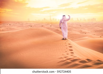 Arabic man with traditional emirates clothes walking in the desert