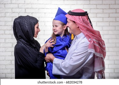 Arabic Middle Eastern family posing with graduated daughter on white background.