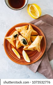 Arabic and middle eastern food concept. Fatayer sabanekh - traditional arabic spinach triangle hand pies dates and tea on a white stone background. Top view.