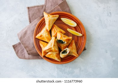 Arabic and middle eastern food concept. Fatayer sabanekh - traditional arabic spinach triangle hand pies  on a white stone background.