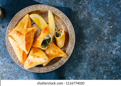 Arabic and middle eastern food concept. Fatayer sabanekh - traditional arabic spinach triangle hand pies on a blue stone background.