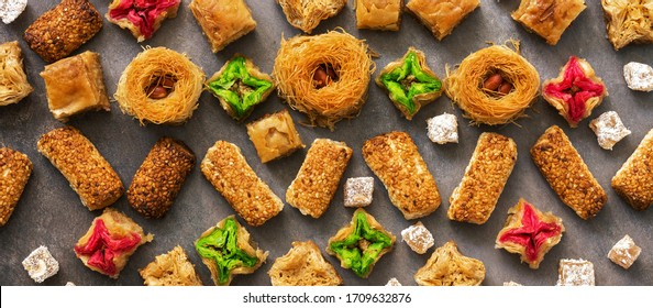 Arabic, Middle Eastern and Turkish dessert, banner. Baklava, cookies with sesame seeds and Turkish delight. Flat lay, top view, border