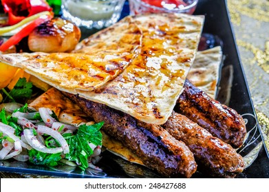 Arabic mixed barbeque plate with sauces and multiple garnish