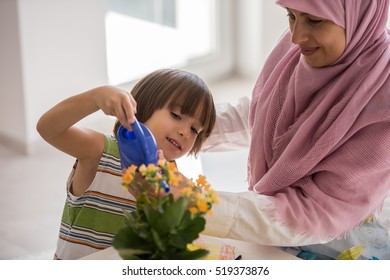 Arabic mother with little son in living room watering flowers