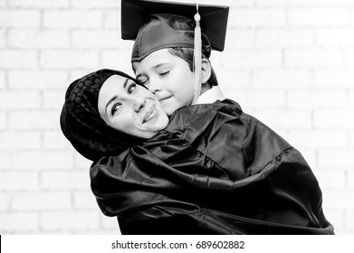Arabic mother posing with graduated son on white background.
