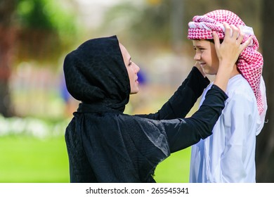 Arabic mother and son outdoors.