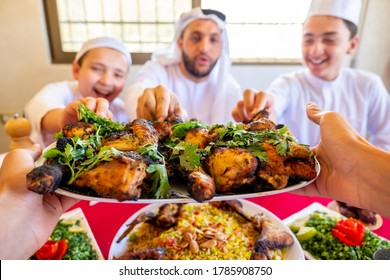 Arabic muslim family being picking chicken from plate being served for them