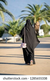 Arabic Muslim girl wearing black robe on the street. Silhouette of arab woman in traditional muslim black hijab or jilbab. Back view.