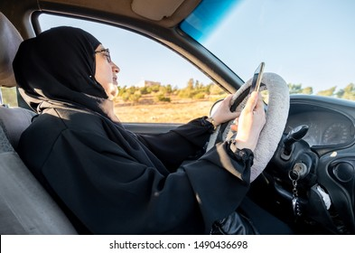 Arabic muslim woman driving a car while using her smart phone