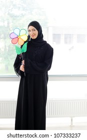 Arabic Muslim woman holding a flower and smiling
