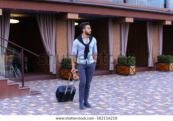 Arabic Muslim Young Man Coming Out of Corner and Goes With Travel Bag to Modern Restaurant, Stopped and Smiling, Holding Black Suitcase. Handsome Muscular Guy Dressed in Black Classic Trousers, White