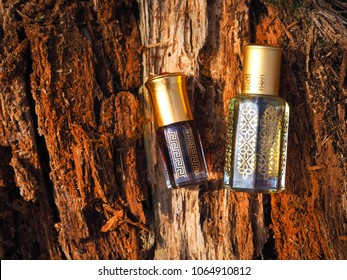 Arabic oil Oud natural background of tree bark. Arabian oud attar perfume or agarwood oil fragrances in mini bottle.