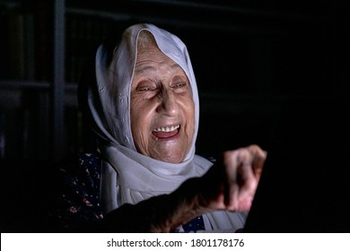 Arabic old muslim woman using her tablet at dark room
