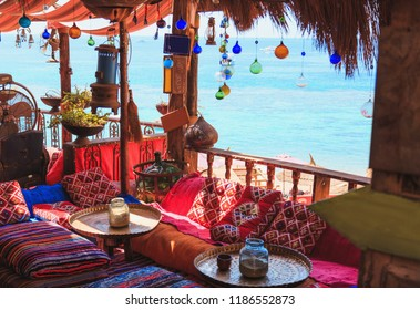 Arabic oriental cafe or hookah with trestle beds and colorful pillows on the sea coast
