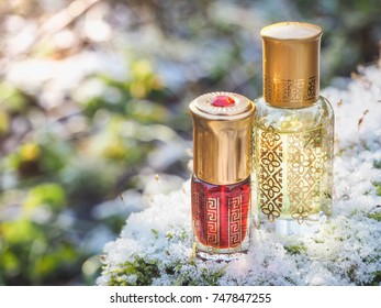 Arabic perfume on a winter background. Scented oil in mini bottles.