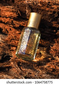 Arabic perfume. One Tola of Attar oil, agarwood tree in a mini bottle on a background of bark.