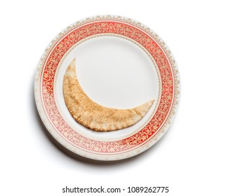 Arabic pita bread or Kuboos in the shape of moon, served on an ornamental plate. View from above. A conceptual photo for a 'food donation ' during festival of Eid.
