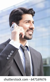Arabic serious smiling happy successful businessman or worker in black suit with tie and shirt with beard calling with his phone near his ear standing in front of an office building.