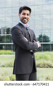 Arabisch ernsthafte lächelnde glückliche Geschäftsmann oder Arbeiter in schwarzem Anzug mit Krawatte und Hemd mit Bart und Arme gekreuzt auf der Brust vor einem Bürogebäude.