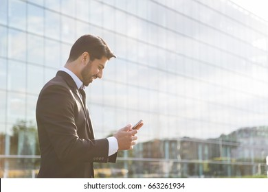 Arabic serious smiling happy successful positive businessman or worker in black suit with beard standing in front of an office glass building and holding a cellphone in his hand in sunny weather.