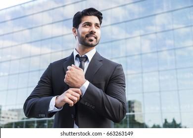 Arabisch ernsthafte lächelnde glückliche positive Geschäftsmann oder Arbeiter in schwarzem Anzug mit Bart steht vor einem Büroglasgebäude und gleicht sein weißes Hemd mit der Hand.
