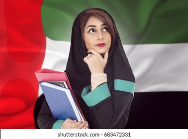 Arabic student wearing hijab and holding a book with UAE flag background