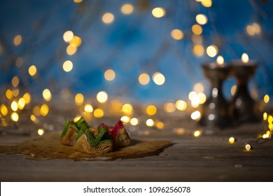 Arabic sweets on a wooden surface. Candle holders, night light and night blue sky with crescent moon in the background.
