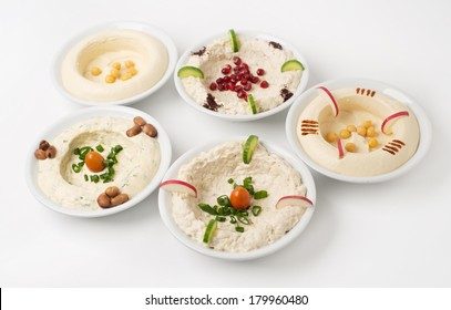 Arabic traditional Hummus Plates with different toppings isolated on white