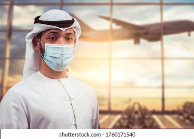 Arabic traveler business man wearing mask waiting to board into airplane, standing in departure terminal in airport.  Arab passenger traveling by plane transportation during covid19 virus pandemic.