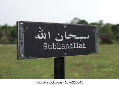"""An Arabic verse signpost with background of a park. Subhanallah is an Arabic verse in Islamic practice that means """"Glory be to Allah""""."""