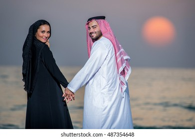 Arabic way dressed couple posing on the beach.Middle Eastern couple.