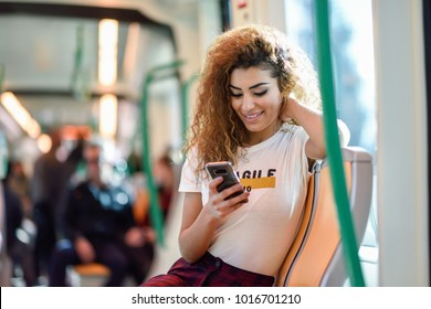 Arabic woman inside subway train looking at her smart phone. Arab girl in casual clothes.