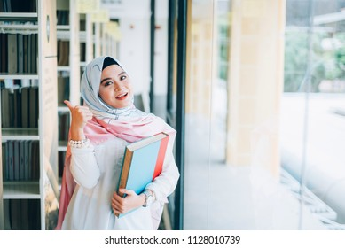Arabic woman taking notes preparing exam and learning lessons from a book at library.