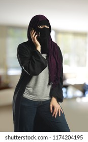 Arabic woman wearing a burqa on the cell phone inside a building