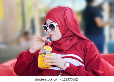 Arabic woman wearing modern abaya and Hijab, Drinking Orange Juice on coffeshop