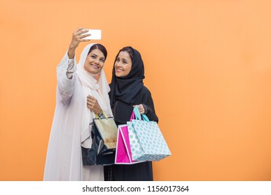 Arabic women shopping outdoors in Dubai - Girls with traditional arabian dress having fun