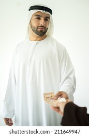 Arabic young businessman making deal and receaving money