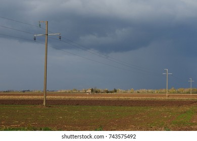 arable land before thunderstorm with electric pillars