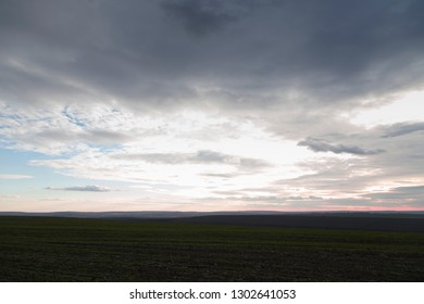 Arable land and the pink sunset with clouds. This is a unique natural phenomenon.