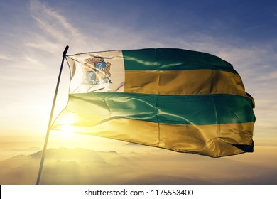 Aracaju city of Brazil flag textile cloth fabric waving on the top sunrise mist fog