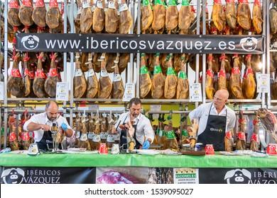 Aracena, Huelva, Spain - October 20, 2019: Butchers slicing slices of a spanish iberian serrano ham with a Exhibitor of cured iberico ham in the background in 2019 iberico ham fair of Aracena