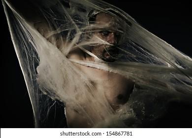 Arachnids, naked man caught in spider web