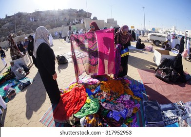 ARAFAT, SAUDI ARABIA-CIRCA MAY 2015:Two unidentified women bargaining clothes at Mount Arafat (or Jabal Rahmah) on May,2015 in Arafat,Saudi Arabia.Muslims believe it is here prophet Adam & Eve met