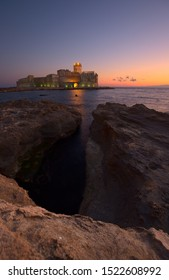 the aragon castle of le  castella with some green lights at the sunset with a massive rock on the foreground.