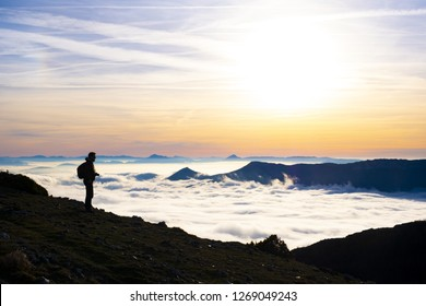 ARALAR, SPAIN - December 23, 2018: Man walking among mountains with a sea of clouds and the morning sun