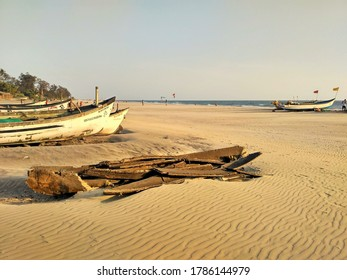 Arambol, Goa / India - April 26, 2020: View of an the wooden remnants of a fishing boat with more fishing boats and ocean in the background